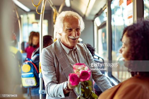 senior man giving his wife a rose - charming stock pictures, royalty-free photos & images