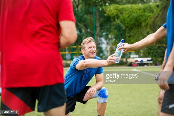 Senior man giving water bottle to friend on the ground