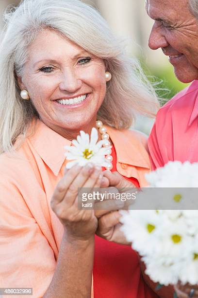Senior man giving wife a flower from bouquet