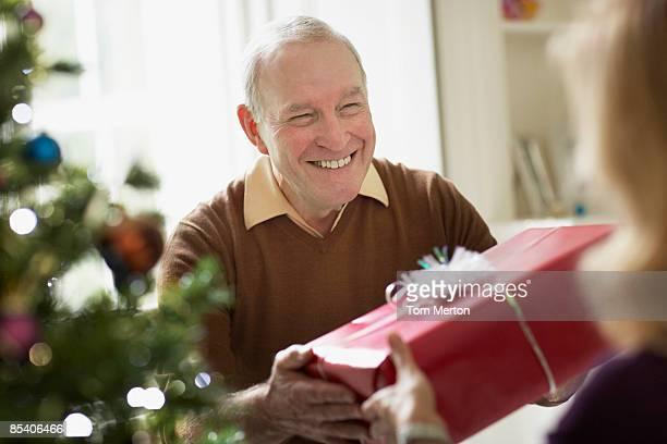 Senior man giving wife Christmas gift
