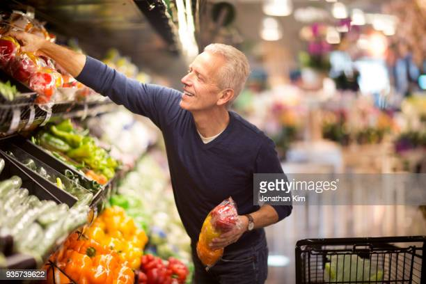 senior man goes grocery shopping. - groceries stock pictures, royalty-free photos & images