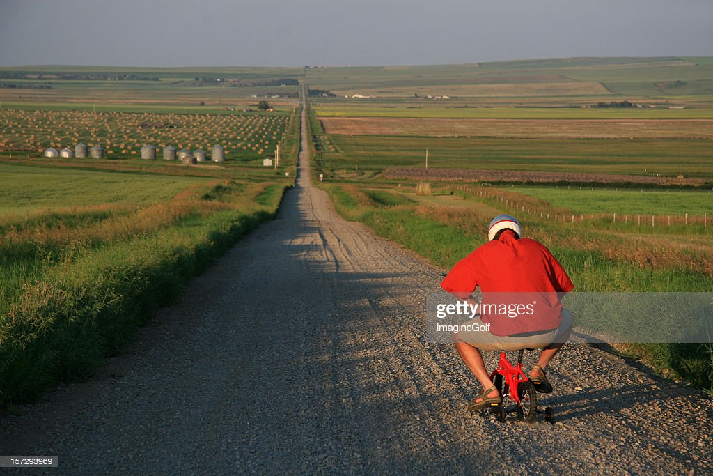Senior Man Going for a Bicycle Ride on Tiny Bike : Stock Photo