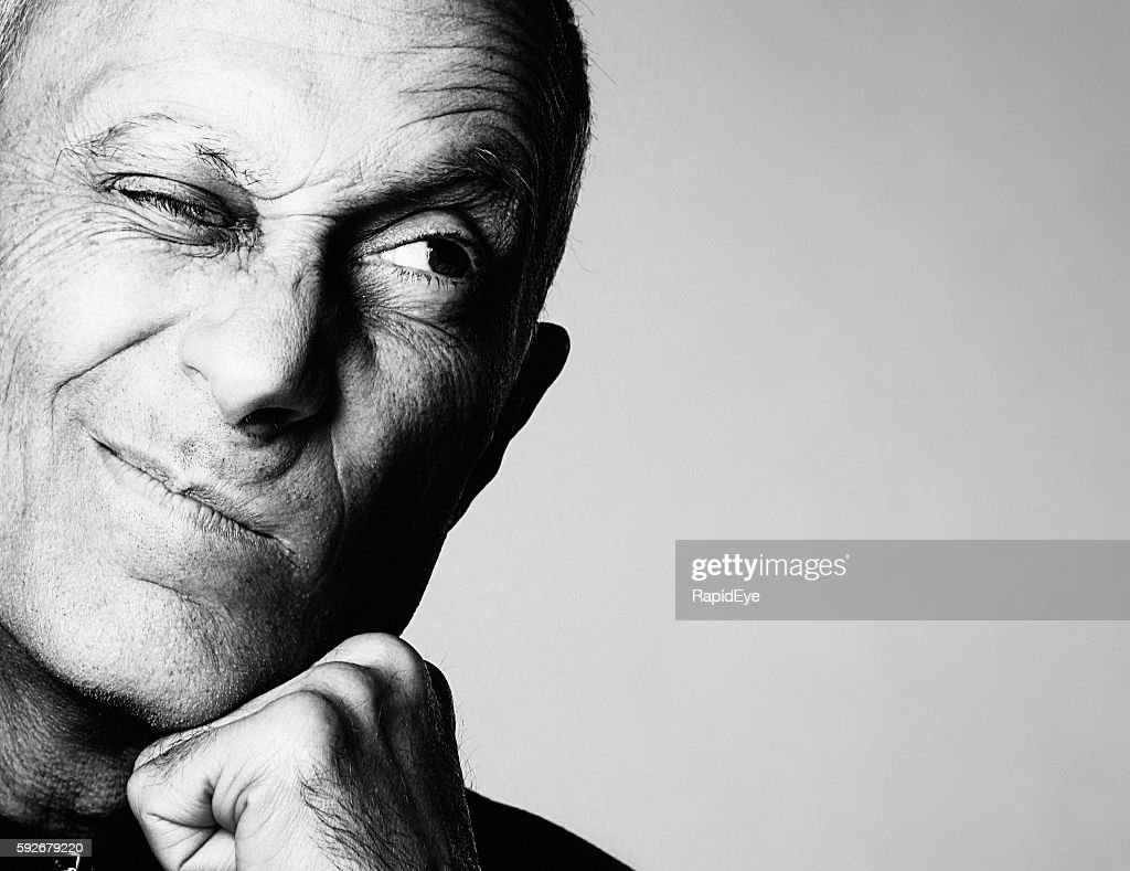 Senior man grimaces cynically looking to the side : Stock Photo