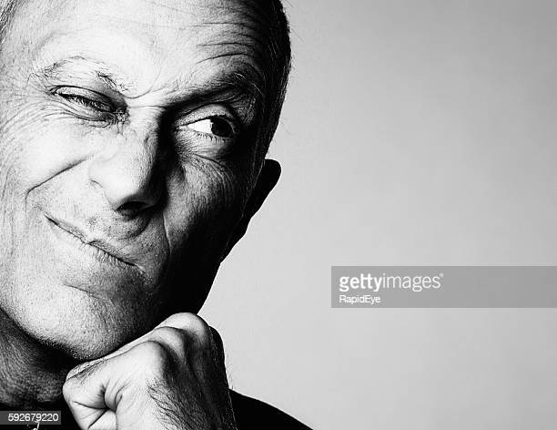 senior man grimaces cynically looking to the side - curiosity stock photos and pictures