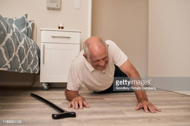 senior man grimacing in pain after a fall - falling stock pictures, royalty-free photos & images