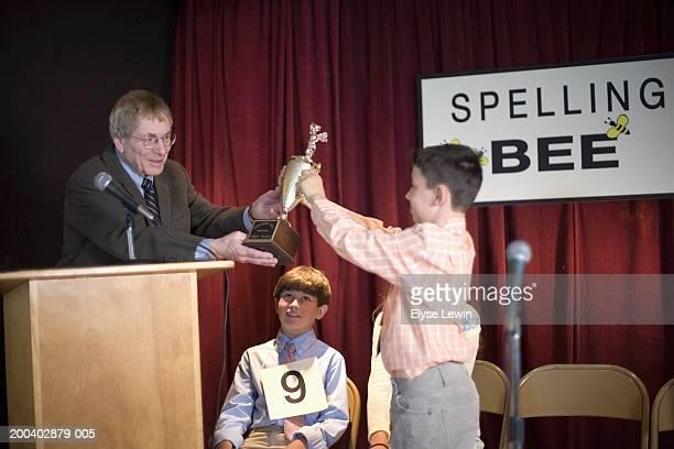 Senior man handing spelling bee trophy to boy (9-11)