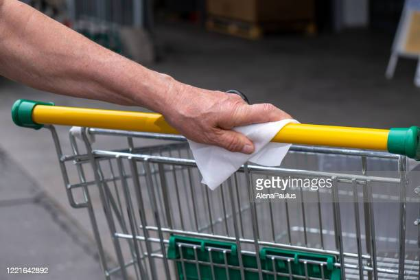 senior man hands close up disinfecting handle from shopping cart - wet wipe stock pictures, royalty-free photos & images