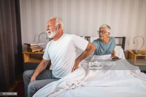senior man having a backpain while waking up next to his worried wife - hypochondria stock photos and pictures