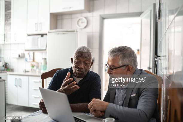 senior man having a consultation with a financial advisor at home - finance and economy stock pictures, royalty-free photos & images