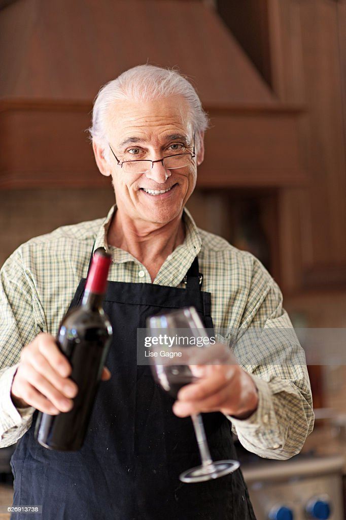 Senior man having a glass of wine : Stock Photo