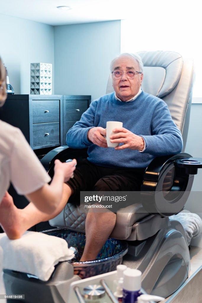 Senior man having a pedicure in a beauty spa. : Stock Photo