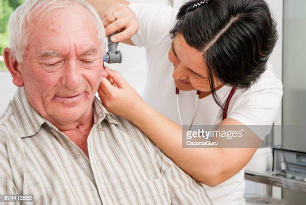 Senior Man Having An Ear Exam In The Doctor's Office