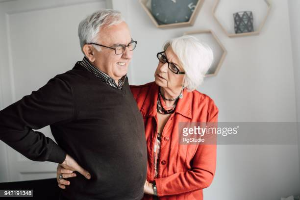 senior man having back pain issues, wife helping him - back pain stock pictures, royalty-free photos & images