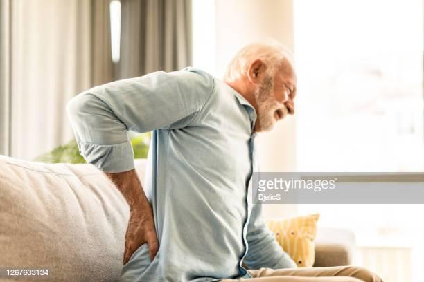 再び腰痛を持つ先輩男性。 - 下背部痛 ストックフォトと画像