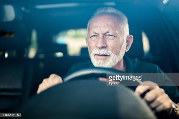 senior man having bad eye sight and making effort to see the road. - eyesight stock photos and pictures