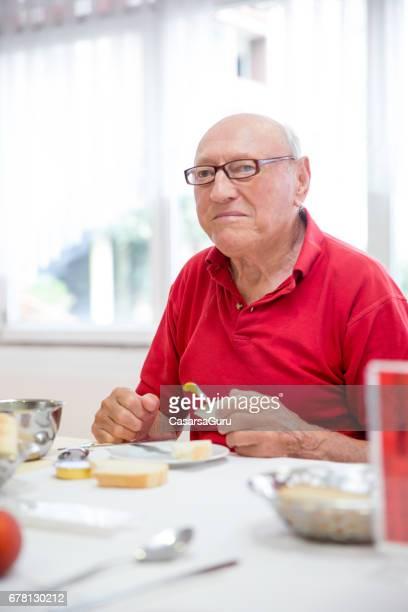 Ein Senior Mann frühstücken