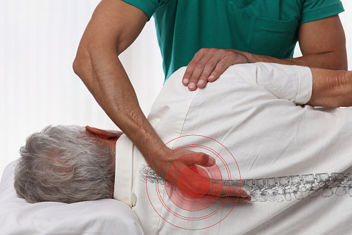 Senior man having chiropractic back adjustment. Osteopathy, Physiotherapy, pain relief concept 898597376