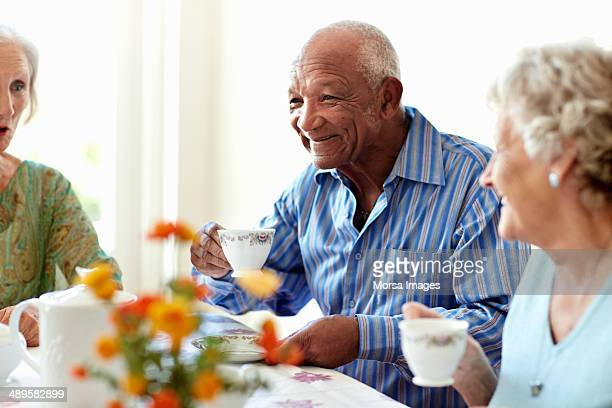 senior man having coffee with friends - retirement community stock pictures, royalty-free photos & images