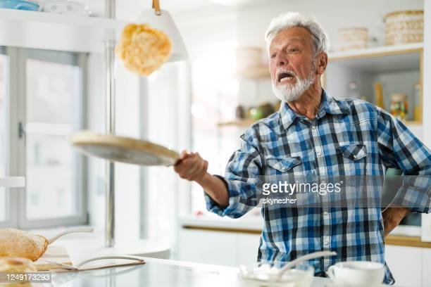 senior man having fun while making pancakes in the kitchen. - pancakes stock pictures, royalty-free photos & images