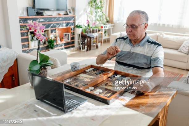 senior man having great time , playing backgammon - game night leisure activity stock pictures, royalty-free photos & images