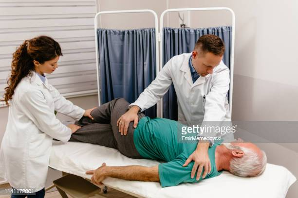senior man having his back examined by a doctor - sciatic nerve stock pictures, royalty-free photos & images