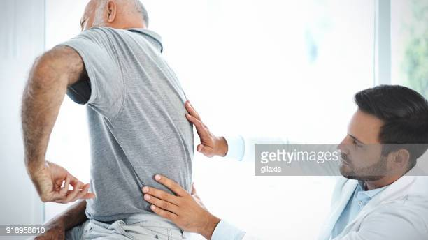 senior man having his back examined by a doctor. - sciatic nerve stock pictures, royalty-free photos & images