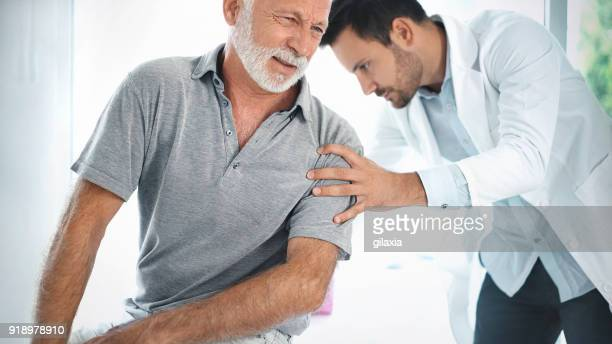 senior man having his back examined by a doctor. - sciatic stock photos and pictures