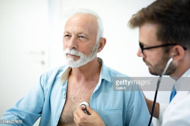 senior man having his heart examined with stethoscope in hospital. - human heart stock pictures, royalty-free photos & images