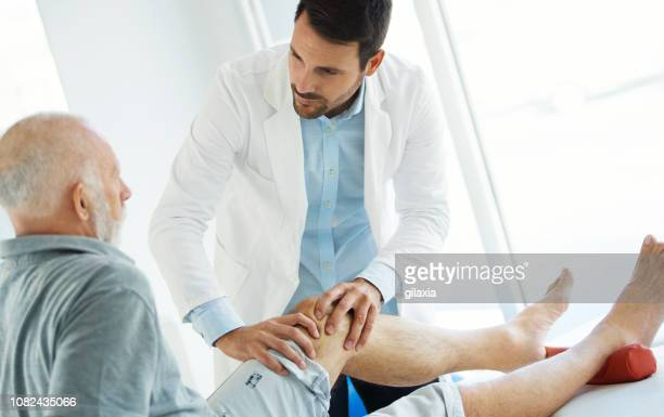 Senior man having his knee examined by a doctor.