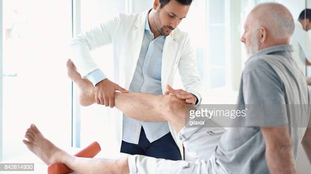 Senior man having his knee examined.