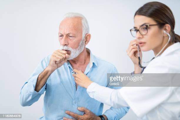 senior man having his lungs examined with stethoscope. - cough stock pictures, royalty-free photos & images