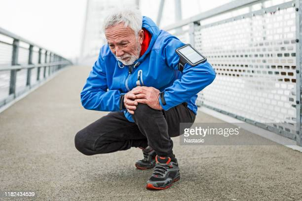senior man having knee injury after running - pain stock pictures, royalty-free photos & images