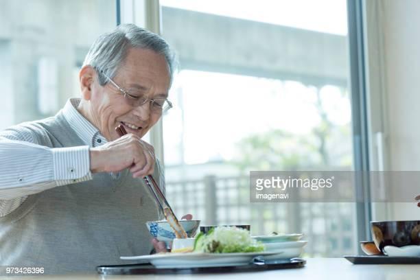 senior man having meal - 食事 ストックフォトと画像