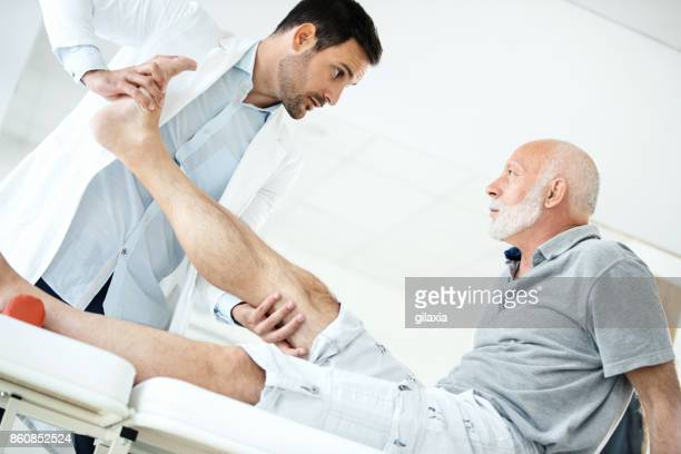 senior man having medical exam. - achilles tendon stock pictures, royalty-free photos & images