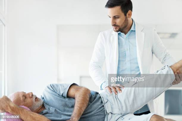 senior man having medical exam. - massage therapist stock pictures, royalty-free photos & images