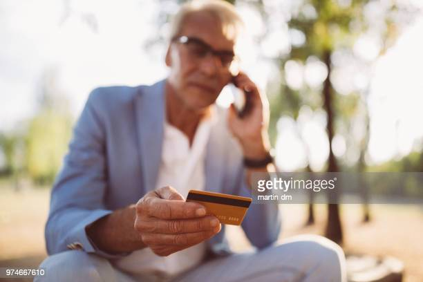 senior man having problems with credit card phoning the bank - fraud stock pictures, royalty-free photos & images