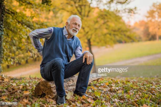 senior man having strong back pain. - back pain stock pictures, royalty-free photos & images