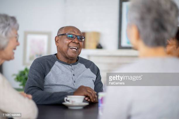 senior man having tea with friends - retirement community stock pictures, royalty-free photos & images