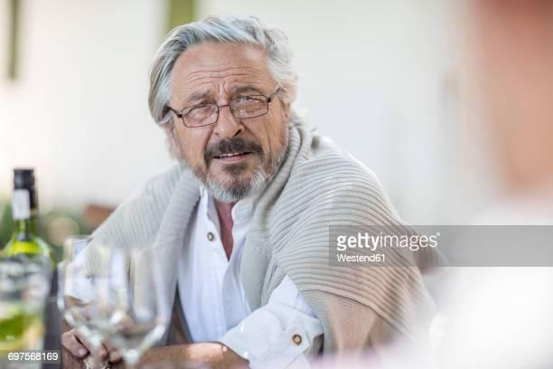 Senior man having wine in garden