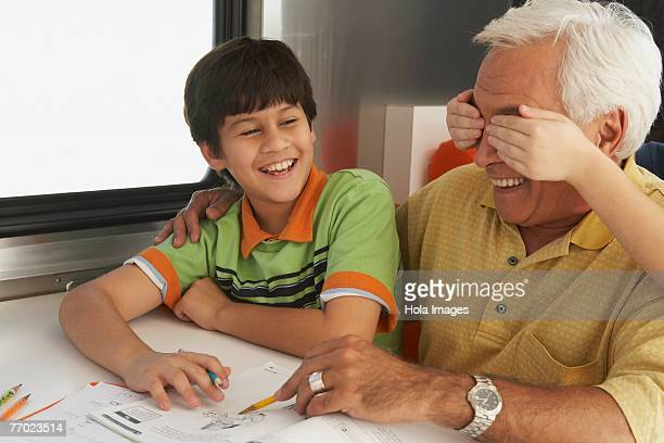 Senior man helping his grandson in his homework and a child's hands covering his eyes from behind
