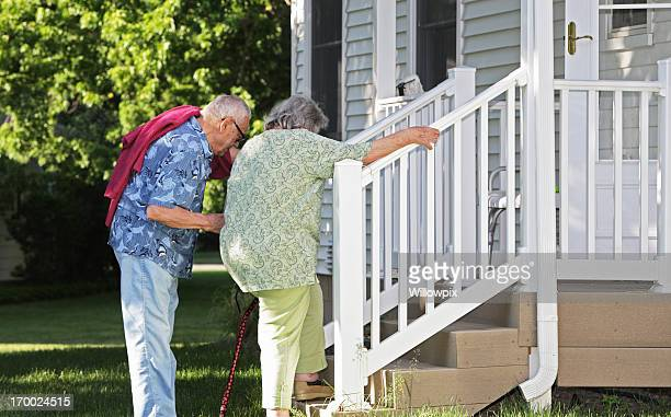 senior man helping wife climb stairs - fat old lady stock photos and pictures
