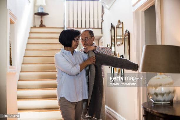 Senior man helping wife with coat