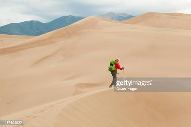 senior man hikes windswept ridge on sand dune - great sand dunes national park stock pictures, royalty-free photos & images