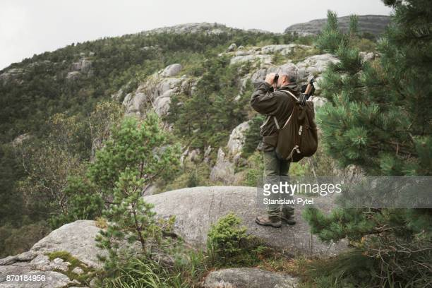 Senior man hiking in mountains looking through binocular