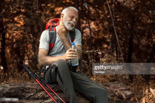 senior man hiking taking a break drinking water defending from mosquito - tick bite stock pictures, royalty-free photos & images