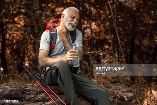 senior man wandelen het nemen van een pauze drinken water verdedigen tegen muggen - insectenbeet stockfoto's en -beelden