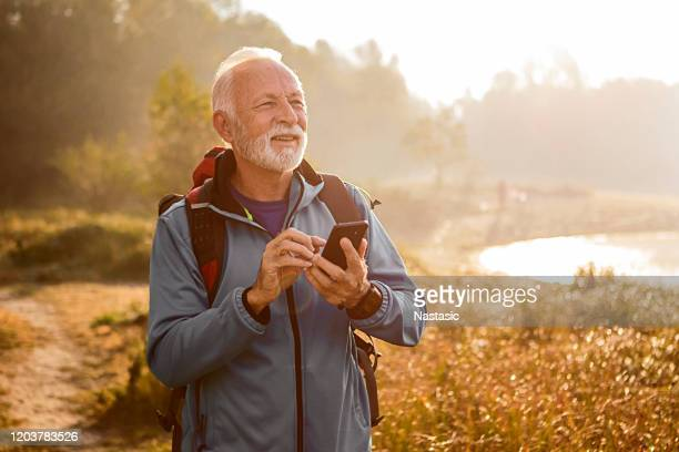 senior man hiking using smart phone - three quarter length stock pictures, royalty-free photos & images
