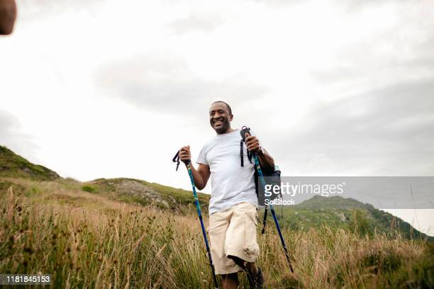 senior man hiking with sticks in the mountains - black ethnicity stock pictures, royalty-free photos & images