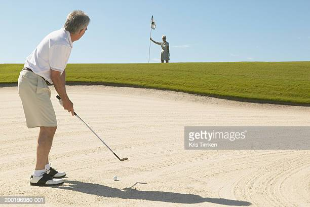 senior man hitting golf ball out of sand trap, woman in background - sand trap stock pictures, royalty-free photos & images