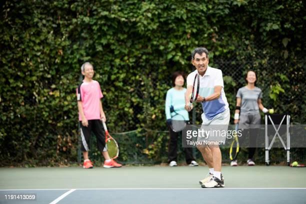 senior man hitting the serve - aufschlagen sport stock-fotos und bilder